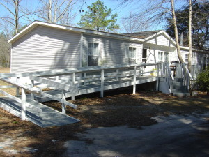 Large white wheelchair ramp attached to a mobile home